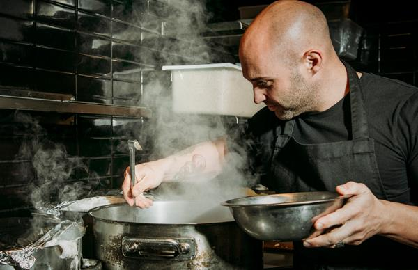 Mid-shot of a male chef in a black apron, stirring a large steel pot, with steam rising from it.