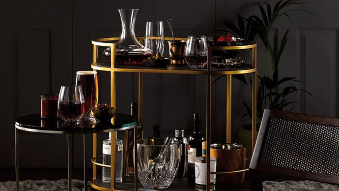 A two-level golden bar cart stocked with bottles of spirits, wine glasses and wine decanter.