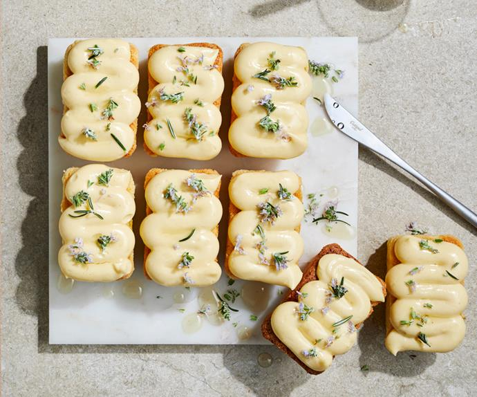 Over-the-top shot of white square plate holding eight small, rectangular shaped cakes topped with squiggles of light-yellow cream, and sprinkled with rosemary leaves and flowers