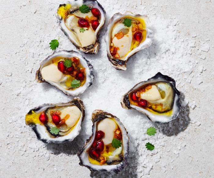 Over the top shot of six shucked oysters, arranged in a circle, on a bed of salt. Each oyster is topped with a pomegranate dressing and tiny green herb leaves.