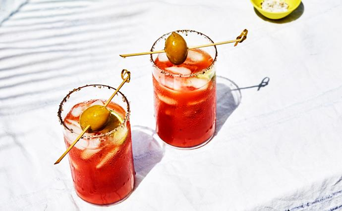 Two clear glasses filled with a red Bloody Mary liquid, topped with green olives on a skewer.
