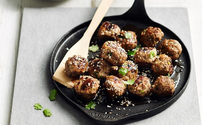 A flat black cast-iron pan with small fried meatballs, sprinkled with white sesame seeds.