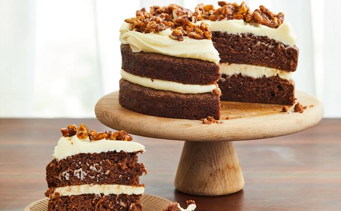 A two-layer carrot cake with cream cheese frosting, topped with walnuts, on a wooden cake stand. A thick triangle slice of carrot cake is in the foreground, on the left.