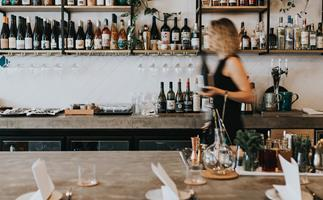 Blonde woman holding a bottle of wine walking behind a restaurant counter.