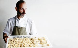 Chef Andreas Papadakis in a white shirt and olive-green apron holding a tray of freshly made pasta.