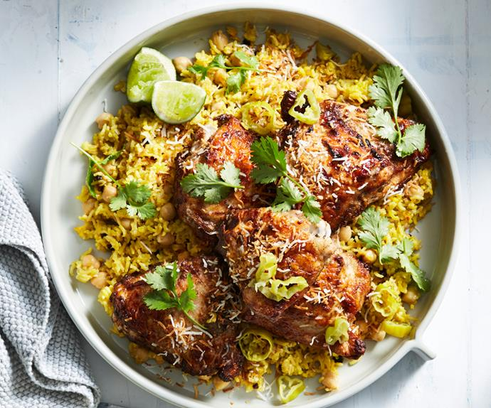 Close-up of a plate of roast chicken thighs on a bed of yellow pilaf, garnished with coriander leaves and lime wedges.