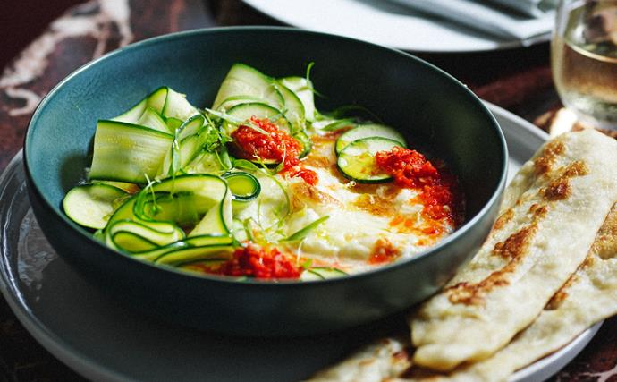 A dark green bowl with baked burrata, chilli sauce and slivers of zucchini, with some flatbread to the side.