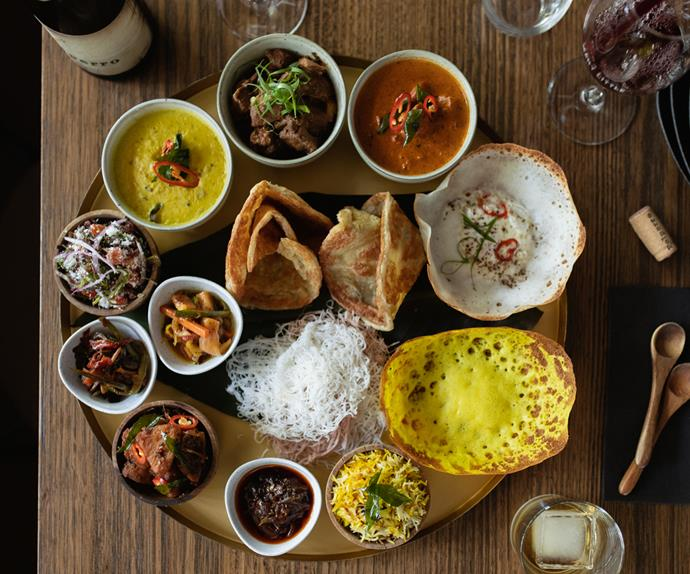 Over-the-top shot of a thali laden with hoppers and small bowls of curries, dhal and pickles.