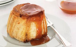 A steamed round apple pudding, drizzled with warm apricot jam, on a round plate with a silver fork on the right.