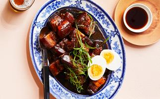 Overhead shot of a ornamental blur and white oval plate holding soy braised pork belly and a halved hard-boiled egg.