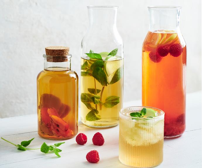 Three glass carafes plus a short ridged glass holding kombucha, garnished with mint and strawberries