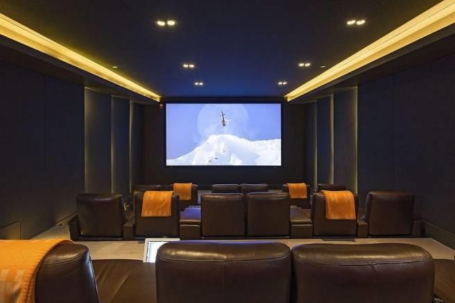 The cozy 24-seat home theater decked out with leather arm chairs is perfect for family movie nights.