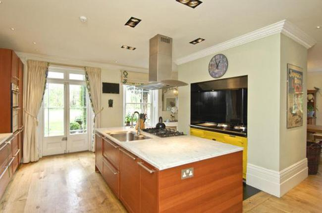 The contemporary kitchen boasts sleek wooden cabinetry, marble countertops and yellow highlights.