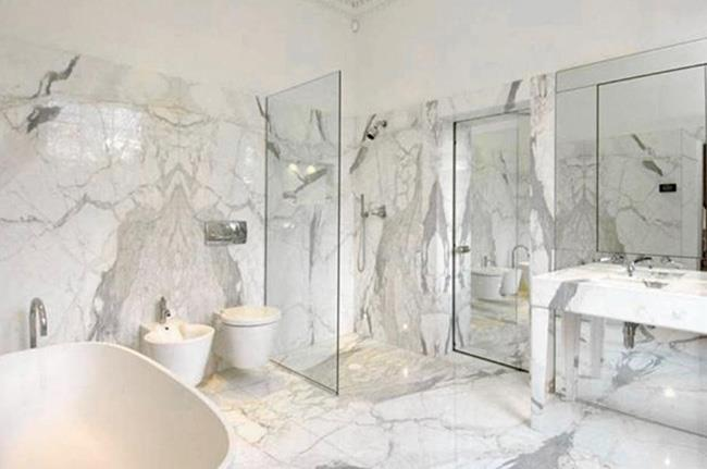 The contemporary bathroom features wall-to-wall marble.