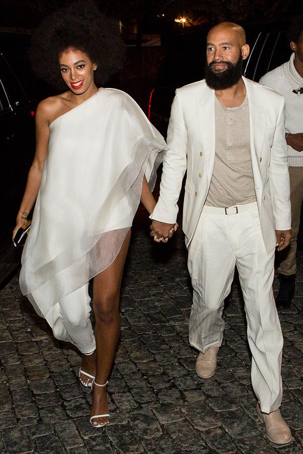 "Knowles and Ferguson looked stunning in their matching white outfits. Knowles was radiant in an asymmetrical, Stéphane Rolland, jumpsuit creation, with elegant ruffle detailing, and white Stuart Weitzman ""Nudist"" heels."