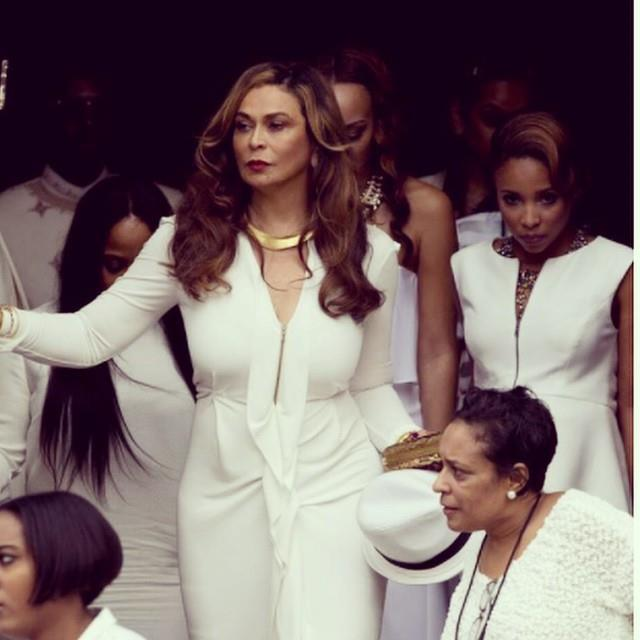 "Mother-of-the-bride, Tina Knowles looked stunning in a floor-length white gown, complete with a thigh split. She accessorised her outfit with gold accents. <br>Photo credit <a href=""http://instagram.com/p/vhEhbTPw5x/?modal=true""> @Beyonce</a>."