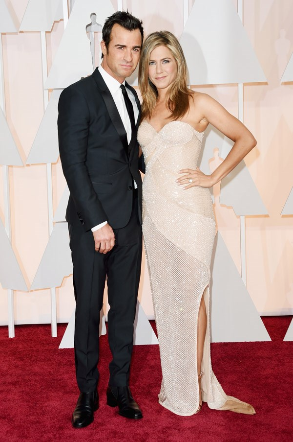 Jennifer Aniston cuddles up to beau Justin Theroux in a custom Versace gown.