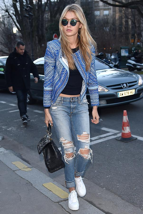 The ultimate transseasonal look, Hadid adds her own flair to the staple jeans, t-shirt and sneakers uniform with a bold jacket and metallic eyewear.