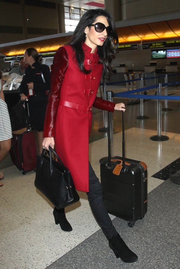 Always one to nail jet-setter chic, Amal rocks a red, Versace coat with a conservative length, while the leather accents and buckle detailing keeps her look fashion forward and on-trend.