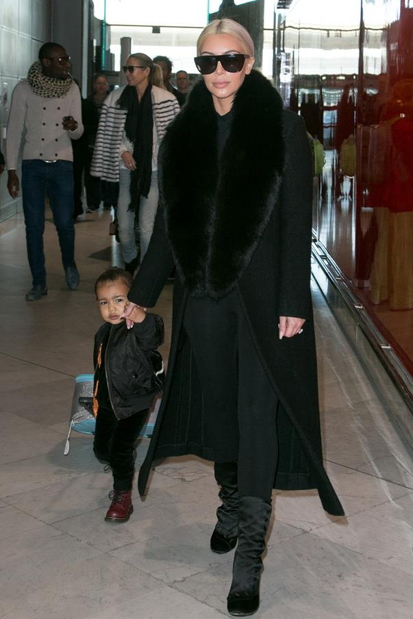 Jet setting in style, Kim travels with daughter North West in an all-black ensemble with an oversized olive fur lapel (12th March 2015).
