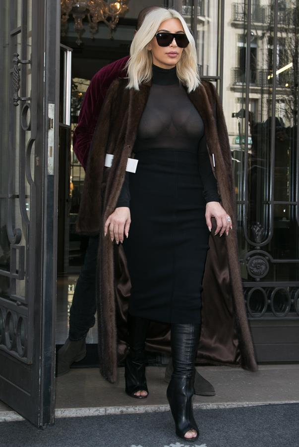 Kim teams a fur coat with a sheer top and black midi skirt outfit while leaving the hotel with Kanye West on March 11th 2015