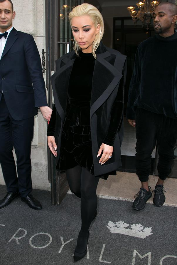 A newly-blonde Kim and husband Kanye wear matching all-black and velvet outfits in Paris before the Balmain Paris Fashion Week show.