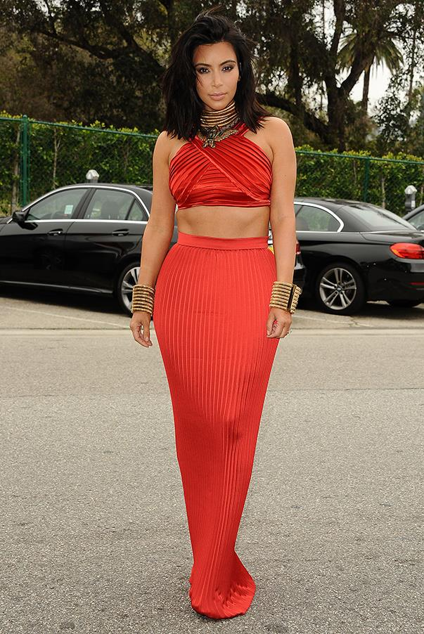 Kim emulates Cleopatra for the ROC NATION GRAMMY Brunch on Feb 7th. The socialite and entrepreneur puts her spin on a traditional, floor length gown, opting for a bright orange two piece with bulky gold, stacked bangles and a stacked, gold chocker neck piece.