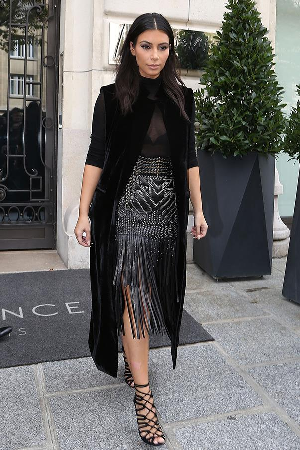 Proving that all black is anything but boring, Kim steps out of her hotel in Paris on the 29th of Sept. wearing a fringe and stud-detail skirt, sheer top sleeveless-blazer.