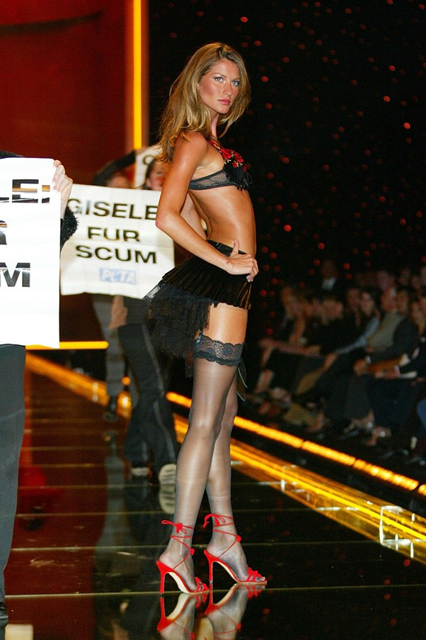 <br><strong>Victoria's Secret</strong> <br><strong><em>2002</em></strong> <br>Gisele makes headlines when PETA protesters storm the VS catwalk. She cements herself as princess of poise and does her thing regardless.