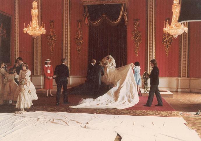 The wedding gown's designers, Elizabeth and David Emanuel, arrange the dress before formal photos.
