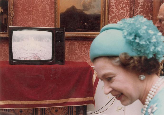 Queen Elizabeth smiles as she watches the TV.