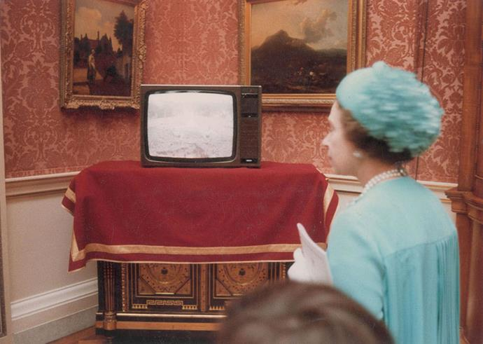 Queen Elizabeth watches the crowds outside Buckingham Palace on TV.