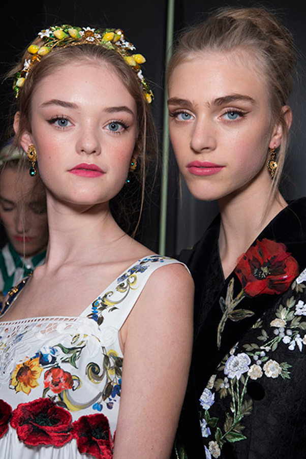 <strong>DOLCE & GABBANA</strong><br><br> The beauty look at Dolce & Gabbana S/S16 took us back to sun-drenched days spent on a beach-bed in the South of Italy. Hair casually thrown up in a loose top knot, and embellished with pretty jewels and headscarfs, plus low-maintenance lip cheek and lip stains patted on with fingers.