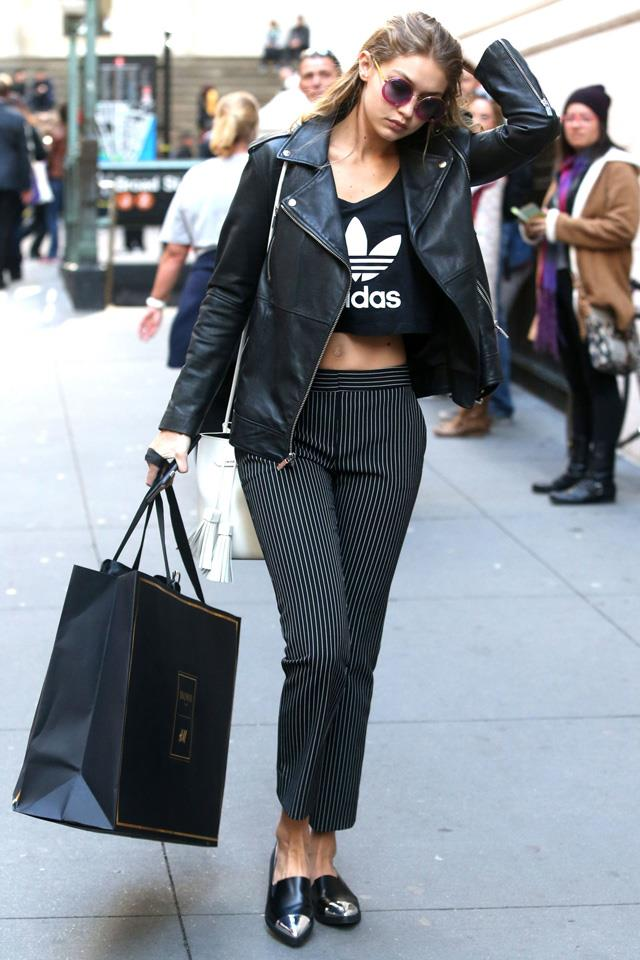 Spotted: Gigi wearing DVF pinstripe pants, an Adidas crop and leather jacket while out in New York.