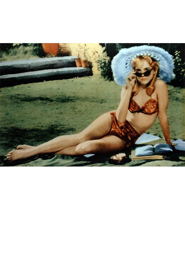 <strong><em>Lolita</em>, 1962<strong> <br><br> Close to 800 girls auditioned for the brazen role of Lolita Haze, but it was former model Sue Lyon who ended up getting the part and creating film history in this scene in which she first meets her older lover in a tropical print hipster bikini, wide-brimmed hat, and cat-eye—not heart-shaped—sunglasses.