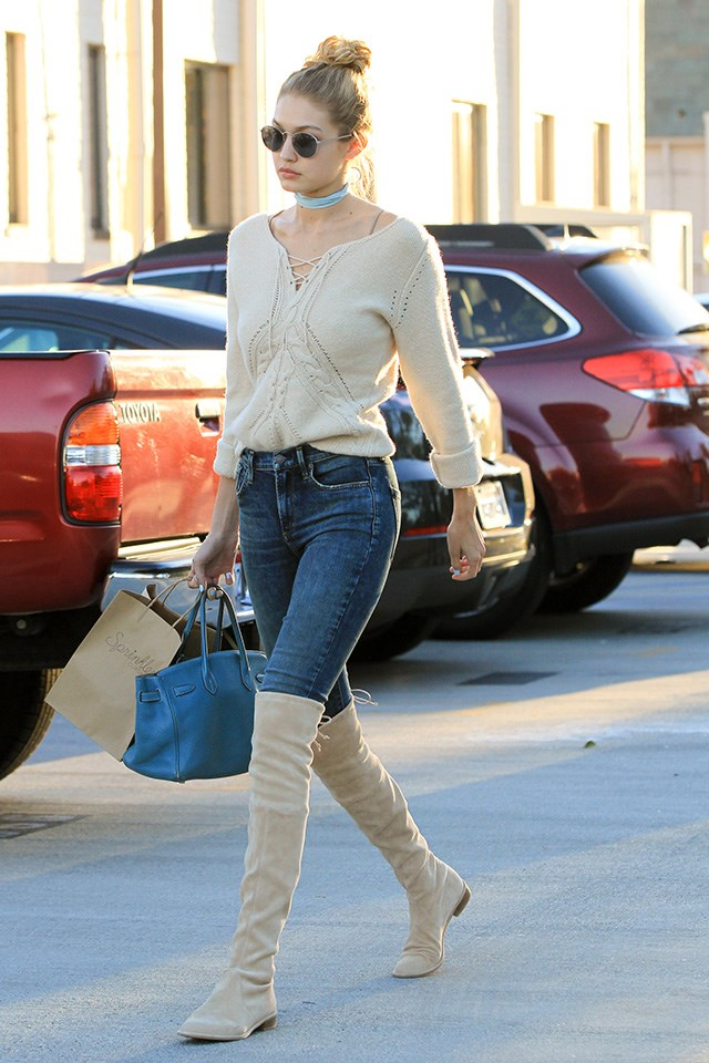 Knee high boots look modern worn over classic skinny jeans thanks to circular shades and a neck-tie.