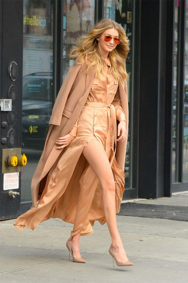 Gigi glowing in a silk nude dress with thigh-high side splits in New York, she's our golden girl.