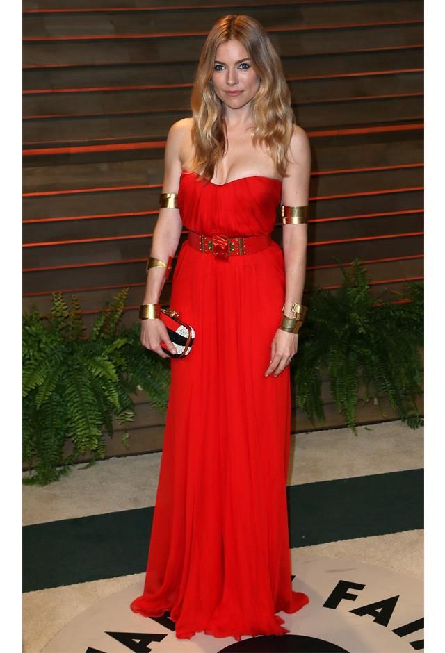 Striking in a red and gold Alexander McQueen get-up at the Vanity Fair Oscar Party, 2014.
