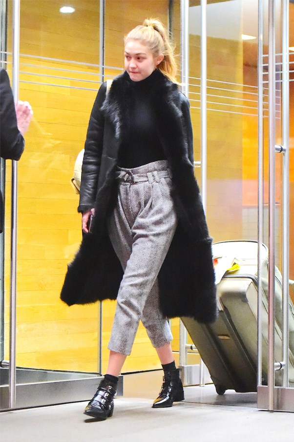 Hadid gives us a lesson in comfort dressing as she steps out of the airport in high--waisted tweed pants, a turtleneck and fur trimmed coat.