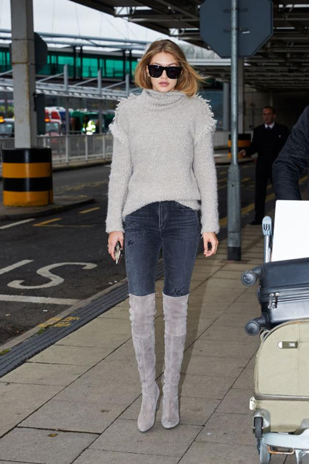 Hadid arriving at London's Heathrow Airport in a grey turtleneck, jeans and suede over-the-knee boots.
