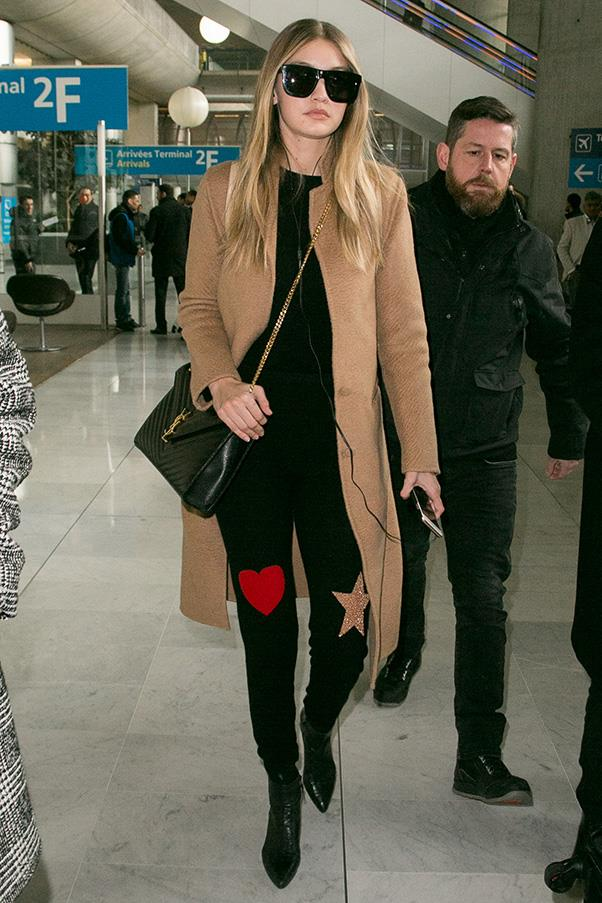 Gigi rocked an playful pair of statement jeans and a chic Saint Laurent bag as she walks through the airport.