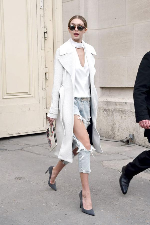 Showing off her toned legs in a pair of super distressed denim jeans, which she pairs with a white top and coat.