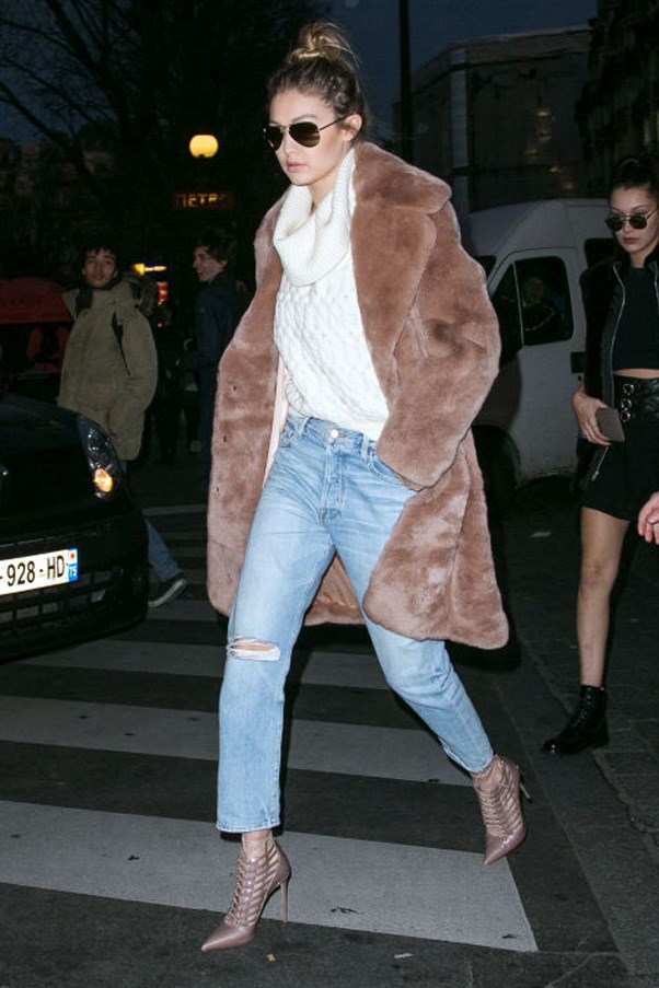 Gigi pulls of the 'cool girl' look effortlessly in turtleneck and fur coat, paired with distressed denim and pointy-toed booties.
