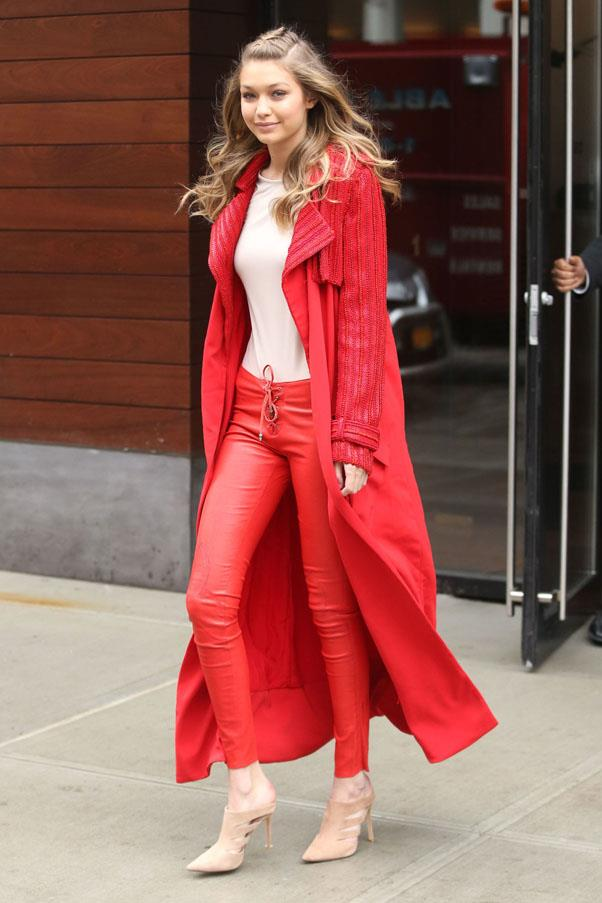 Hadid looks the part of a young supermodel in a monochromatic red ensemble featuring leather pants and long duster coat.