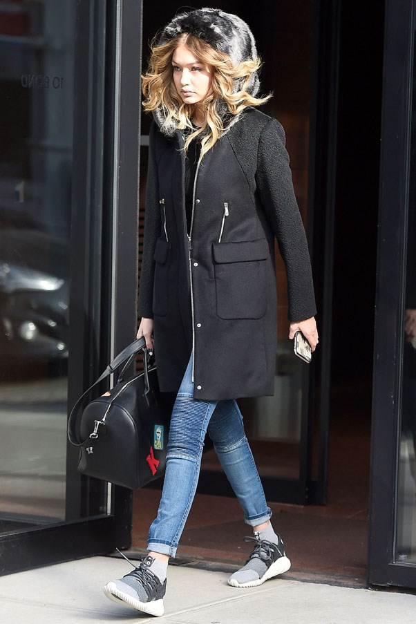 Effortless and chic between NYFW shoes, Hadid steps out in casual jeans, sneakers and a hooded black coat.