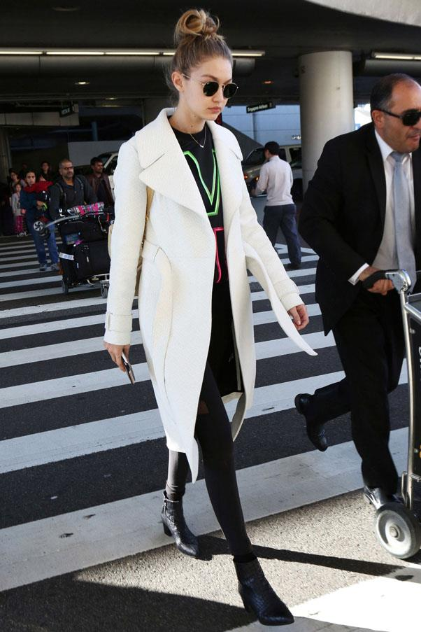 Looking super effortless while stepping out of the airport in a white coat, Versace sweatshirt and leggings.