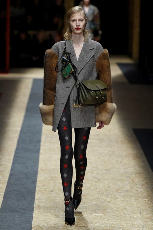 <strong>PRADA</strong><BR><BR> In the days leading up to the show, Prada dropped hints on her Instagram about journeys through dreamy collaged landscapes, strength, femininity and the progression of nature. As esoteric as those Easter eggs were, the audience just experienced raw emotion of desire, of wanting the metallic jacquard skirts and military coats, the argyle gloves (like socks for your hands!), the high-and-tight cross-body bags and the lace-up boots. Everything looked familiar and yet different. A great tailored grey men's coat was spliced with brown mink and thrown over argyle tights—can we get excited now about those tights? Forties-era dresses that Prada loves so much were spotted, too, but done sheer and belted with knitted corsets.