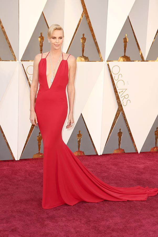 """<strong>Charlize Theron in Dior:</strong> <br><br> """"This Dior dress fits Charlize like a glove. It's dramatic yet understated and is made all the more Oscars-appropriate with the $4 million worth of Harry Winston diamonds she has hanging from her neck and ears."""" - Grace O'Neill, digital content manager <br><br> """"Whoever said you should never wear red on the red carpet needs to see Charlize Theron in red Dior. This is a bona fide movie star, not a prom queen. Also love the Harry Winston diamonds that drop perfectly into that deeper-than-deep V."""" - Kellie Hush, editor in chief <br><br> """"Now THIS is how you dress for the Oscars. Bravo, Charlize."""" - Alison Izzo, digital editor"""