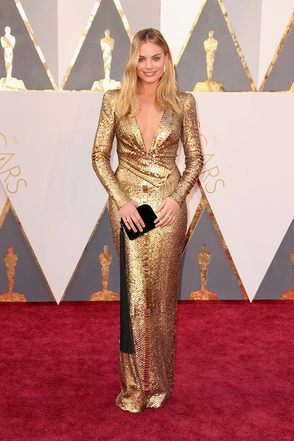 """<strong>Margot Robbie:</strong> <br><br> """"Margot looks like a glowing goddess. Also, bold choice wearing gold as she could look like an Oscar but somehow doesn't. Love the clutch paired with the dress from The Row. It is heavenly and sleek."""" - Caroline Tran, market editor <br><br> """"Margot Robbie may look like an Oscar in this Tom Ford masterpiece, but she is killing it, as per usual."""" - Pete Harrison, group commercial category manager."""