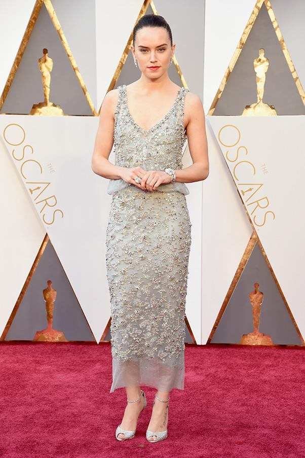"""<strong>Daisy Ridley:</strong> <br><br> """"The shade of grey and embellished detail are so dreamy. I also love the length of the Chanel dress."""" - Caroline Tran, market editor <br><br> """"Embellished and understated and kind of like a pixie. My favourite!"""" - Jessica Matthews, deputy chief sub editor <br><br> """"Newcomer Daisy Ridley earns her red carpet stripes in this chic, embellished Chanel dress. It may be a little too tame for an event as big as the Oscars, but she manages to pull it off."""" - Grace O'Neill, digital content manager <br><br> """"This basically deserves its own award… forget Leo. All hail Daisy!"""" - Anna Lavdaras, beauty writer"""